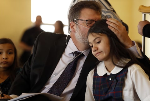 Dean Bortell, front left, kisses his 11-year-old daughter, Alexis, as the 11-year-old medical cannabis refugee from Texas who now lives in Denver waits to testify during a House committee hearing on a pair of bills that would ban co-op pot growing by setting a statewide limit of 12 marijuana plants per residential property Monday, March 6, 2017, in Denver.