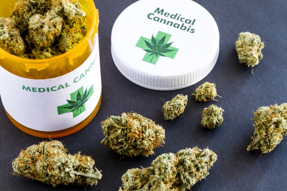 A bottle of medical cannabis on a table, surrounding be buds of dried cannabis.