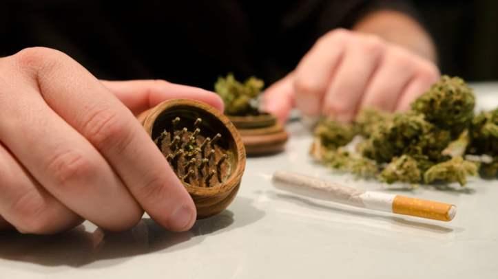 Stock-Man-Preparing-Marijuana-in-Cigarette